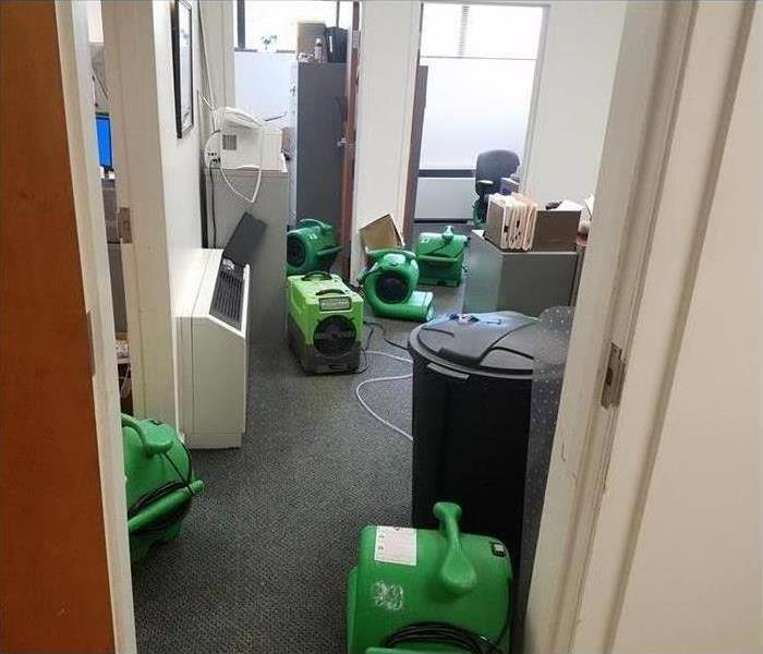 An office that suffered from water damage and many air movers are placed to start drying affected area