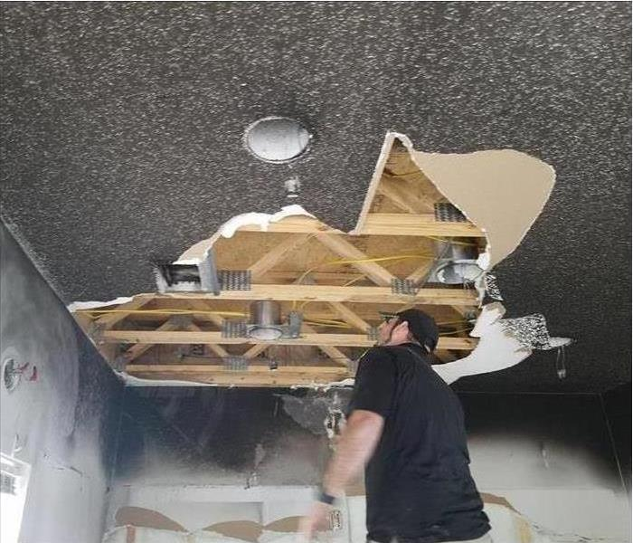 Technician evaluating ceiling after burning